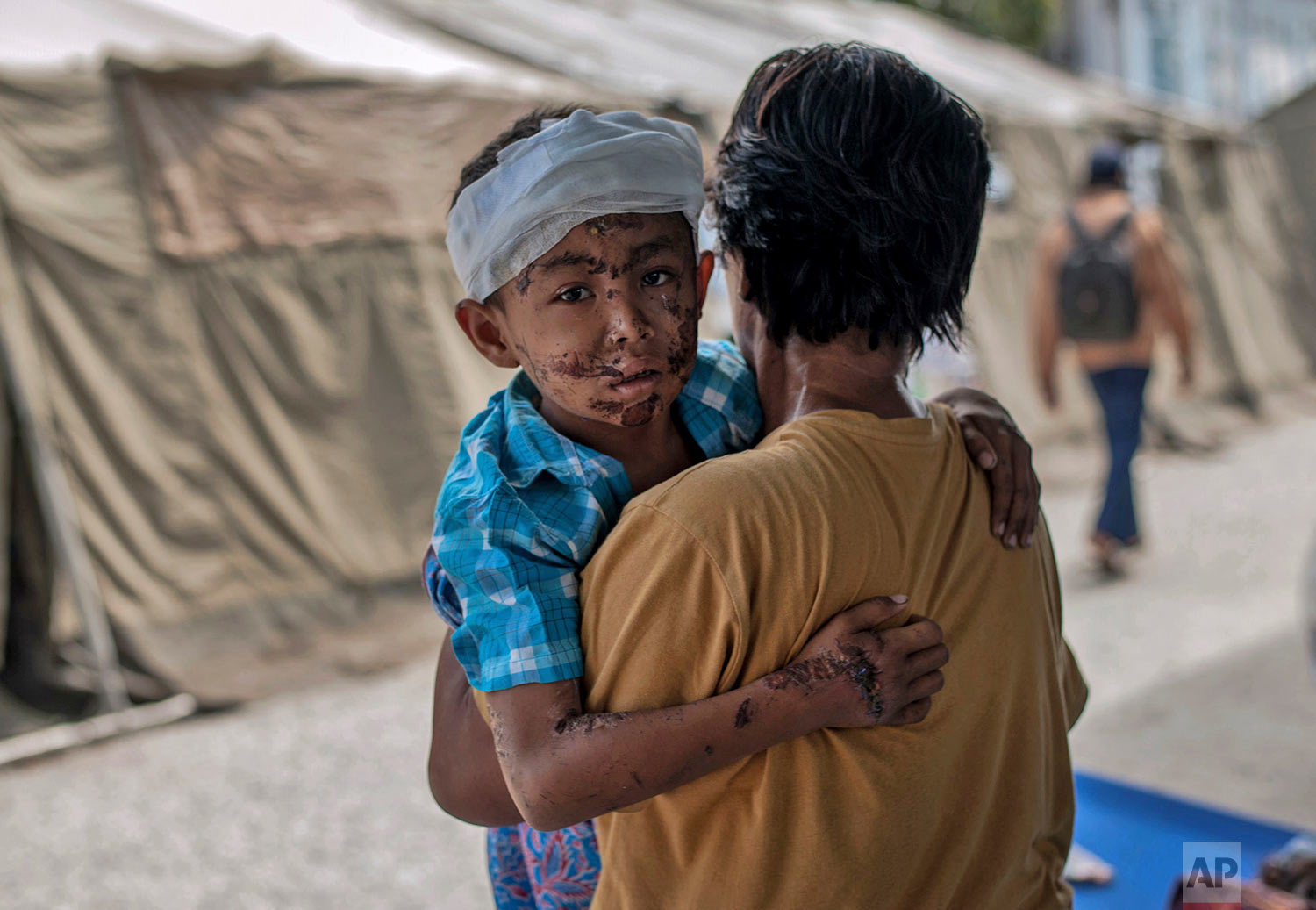 A boy injured during the tsunami is carries by his relative at a makeshift hospital in Palu, Central Sulawesi, Indonesia, Oct. 4, 2018. (AP Photo/Fauzy Chaniago)