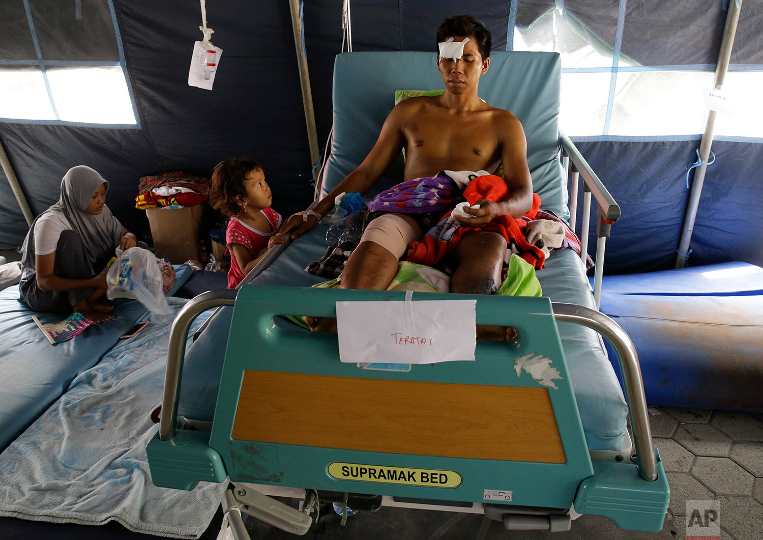 A girl looks at her injured father as he lies on a hospital bed after a massive earthquake and tsunami hit Palu, Central Sulawesi, Indonesia, Oct. 4, 2018. (AP Photo/Aaron Favila)