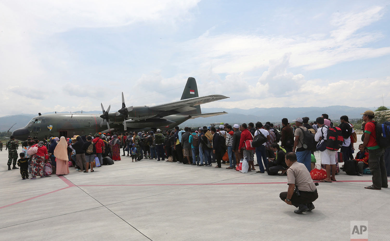 People line up to board an Indonesian Air Force cargo plane at Mutiara Sis Al-Jufri airport as they try to go out of Palu, Central Sulawesi Indonesia, Oct. 4, 2018. (AP Photo/Tatan Syuflana)