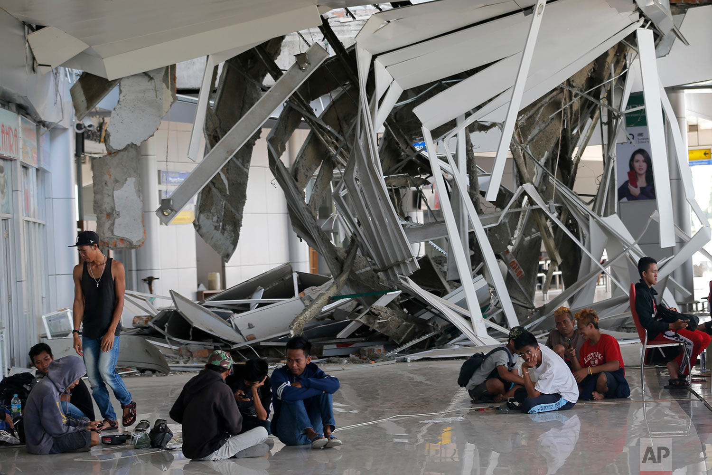 People sit outside Mutiara Sis Al-Jufri airport damaged by a powerful earthquake and tsunami in Palu, Central Sulawesi Indonesia, Oct. 4, 2018. (AP Photo/Tatan Syuflana)