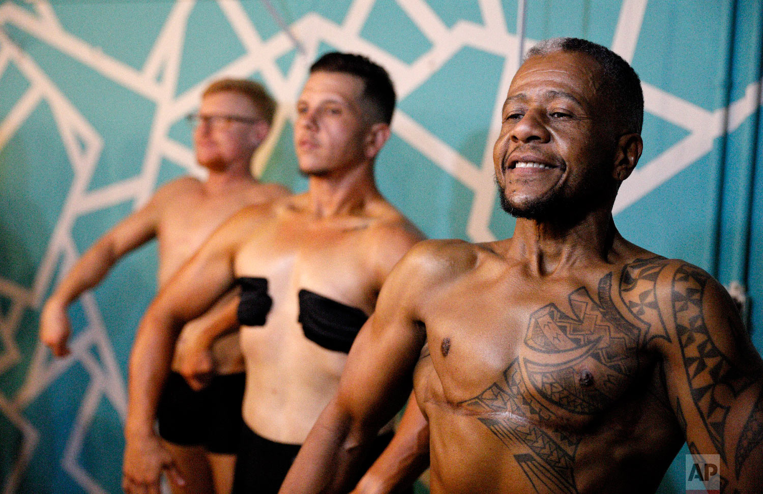 Charles Bennett, from right, of San Francisco, practices a pose in front of a mirror with fellow contestants Devyn Michael Clark, of Jacksonville, Fla., and Peter Moore, of Oakland, Calif., backstage before the start of the International Association of Trans Bodybuilders competition in Atlanta, Oct. 6, 2018. (AP Photo/David Goldman)