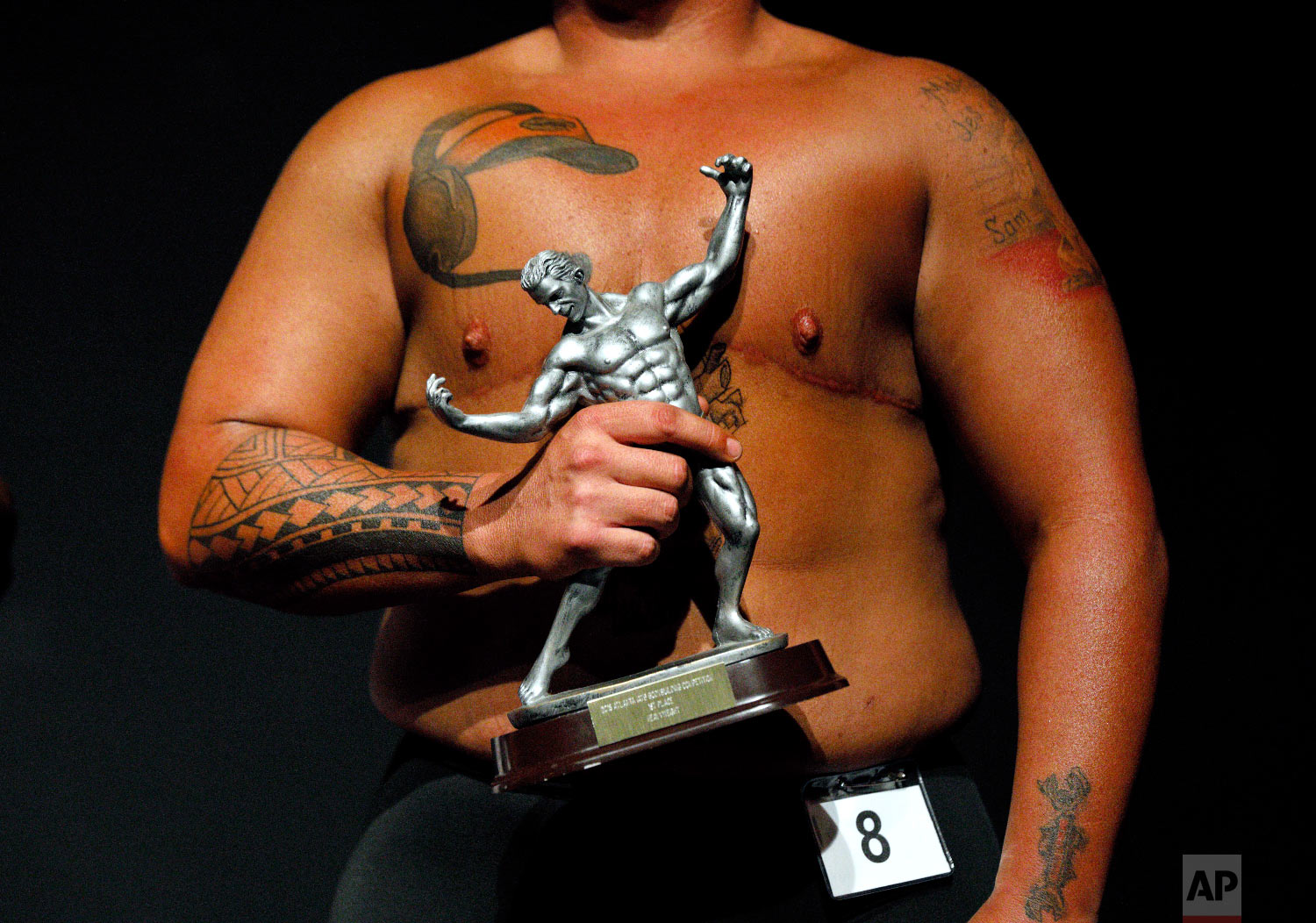 Kennedy Conners, of Conyers, Ga., who transitioned from female a year and half ago, holds his trophy after winning the heavyweight class in the International Association of Trans Bodybuilders competition in Atlanta, Oct. 6, 2018. (AP Photo/David Goldman)