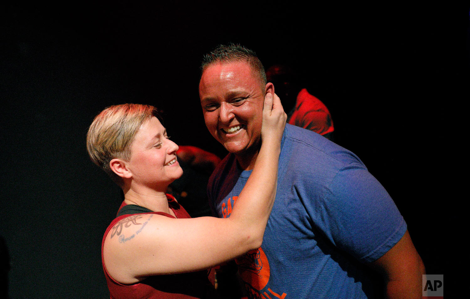 Kennedy Conners, of Conyers, Ga., right, who transitioned from female a year and half ago, is embraced by his wife, Nikki, after performing in the International Association of Trans Bodybuilders competition in Atlanta, Oct. 6, 2018. (AP Photo/David Goldman)