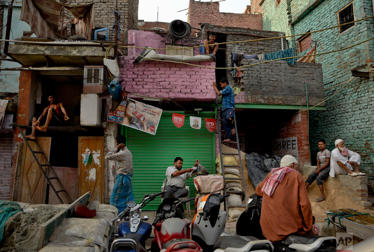 Migrant workers from eastern India prepare themselves for the day outside their cramped accommodations in the old quarter of New Delhi, India, Wednesday, Oct. 10, 2018. Some 800 million people in the country live in poverty, many of them migrating to big cities in search of a livelihood. (AP Photo/R S Iyer)