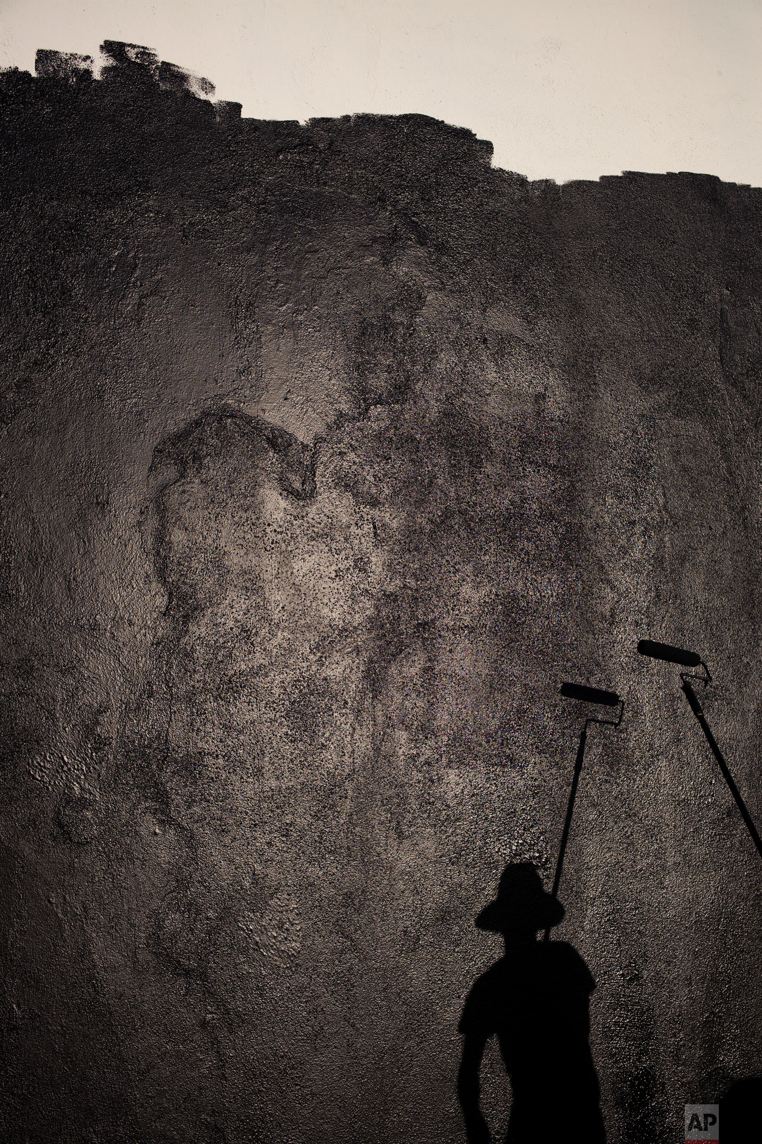 Artist's assistant Matthew Crumpton casts a shadow as he prepares a wall for a mural Monday, Oct. 8, 2018, in Los Angeles. (AP Photo/Jae C. Hong)