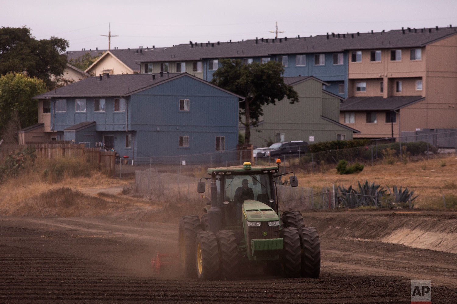 A tractor plows in a field near apartment buildings in Salinas, Calif., on Sept. 5, 2018. (AP Photo/Jae C. Hong)