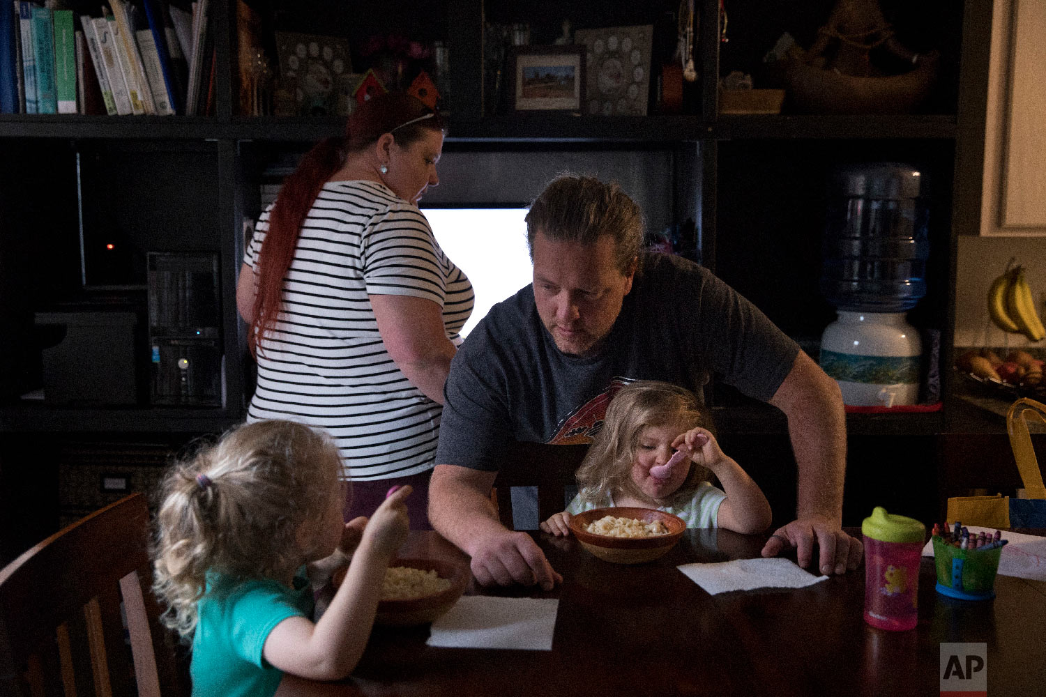 Middle-school English teacher Maryam Powers, left, works on her computer as her boyfriend, Jean-Paul Varagnat, chats with their two daughters around the dinner table in Salinas, Calif., Sept. 5, 2018. (AP Photo/Jae C. Hong)