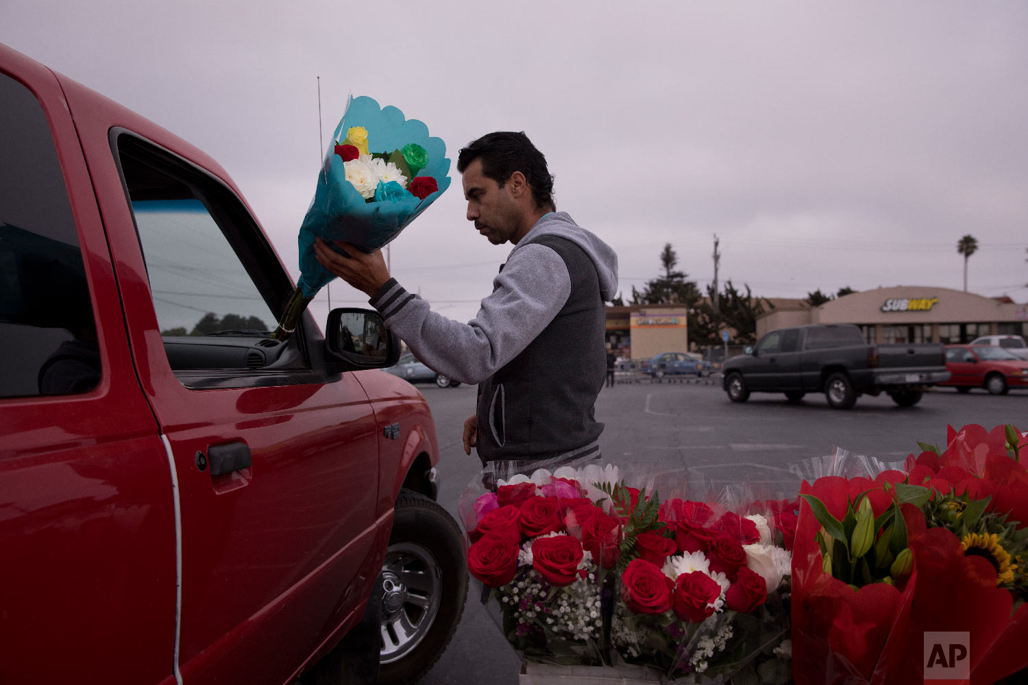 Jose Contrares, 41, who shares an apartment with seven people, sells flowers in the parking lot of a strip mall in Salinas, Calif., Sept. 4, 2018. (AP Photo/Jae C. Hong)