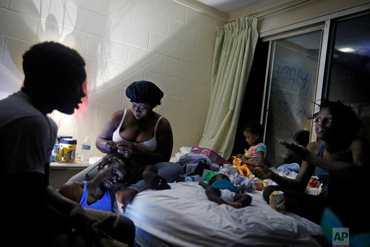 Gabrielle Morgan, center rear, braids the hair of her husband Santional as they sit by a lantern with their children from left, Decoya, 13, Isabella, 3 mos., Gabriella, 3, and Lakevia, 15, in their room at the damaged American Quality Lodge where they continue to live without power in the aftermath of Hurricane Michael in Panama City, Fla., Oct. 16, 2018. (AP Photo/David Goldman)