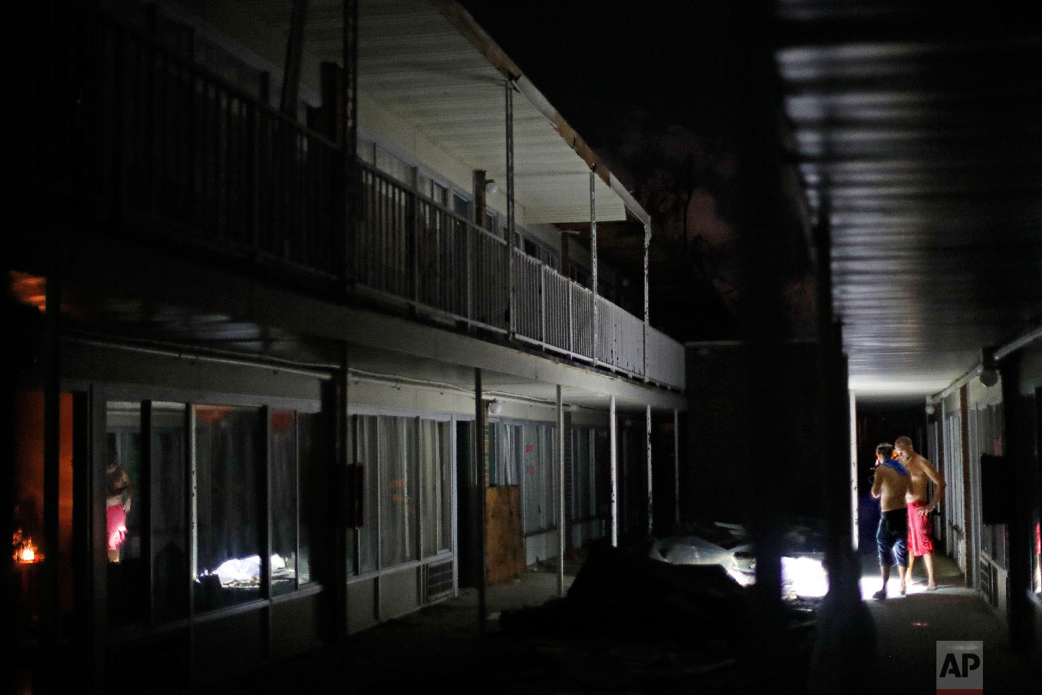 Residents use flashlights to navigate the dark walkways at night at the damaged American Quality Lodge where they continue to live in the aftermath of Hurricane Michael, in Panama City, Fla., Oct. 16, 2018. (AP Photo/David Goldman)
