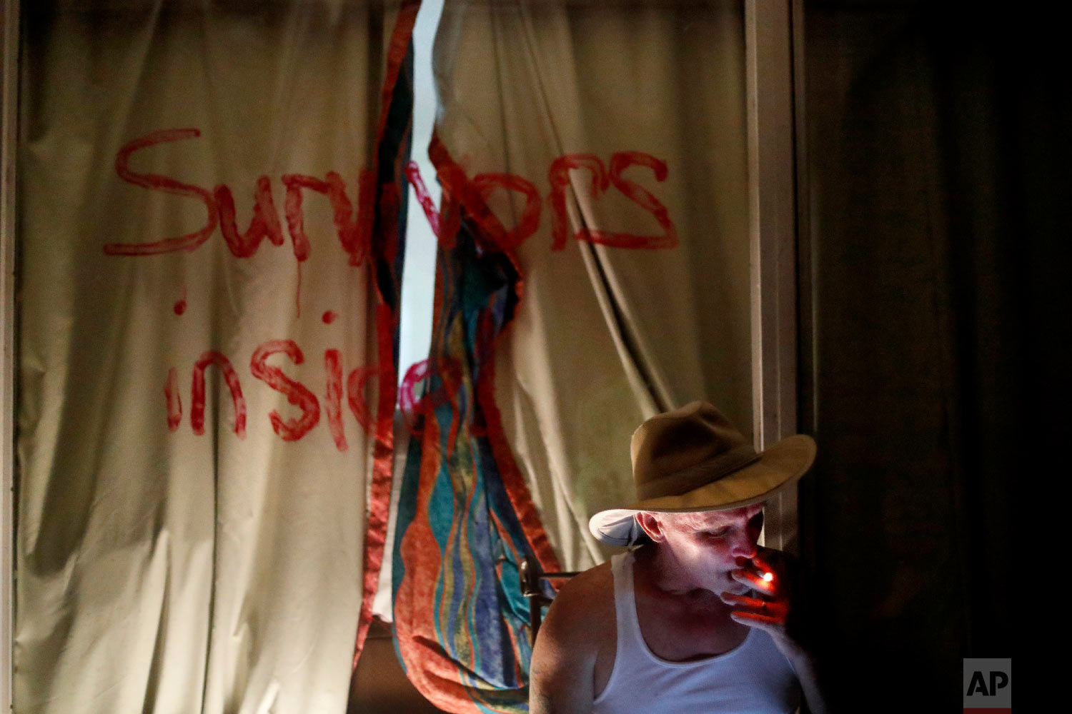 "Wes Allen, Sr., smokes a cigarette outside his room at the damaged American Quality Lodge as the message ""Survivors inside"" is written on the window in the aftermath of Hurricane Michael, in Panama City, Fla., Oct. 16, 2018. (AP Photo/David Goldman)"