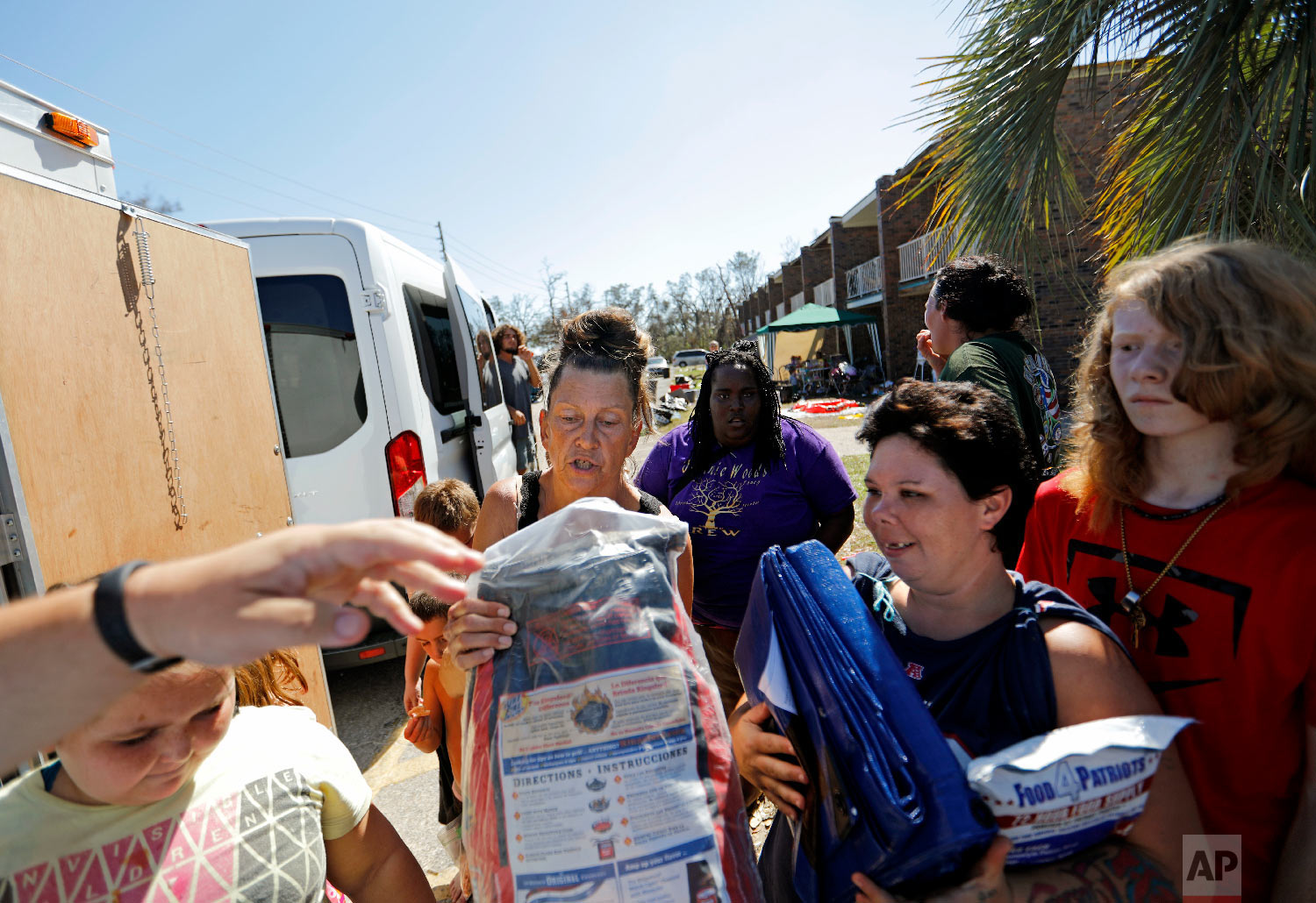 Charcoal, tarps and baby supplies are distributed outside the damaged American Quality Lodge where residents continue to live in the aftermath of Hurricane Michael, in Panama City, Fla., Oct. 16, 2018. (AP Photo/David Goldman)