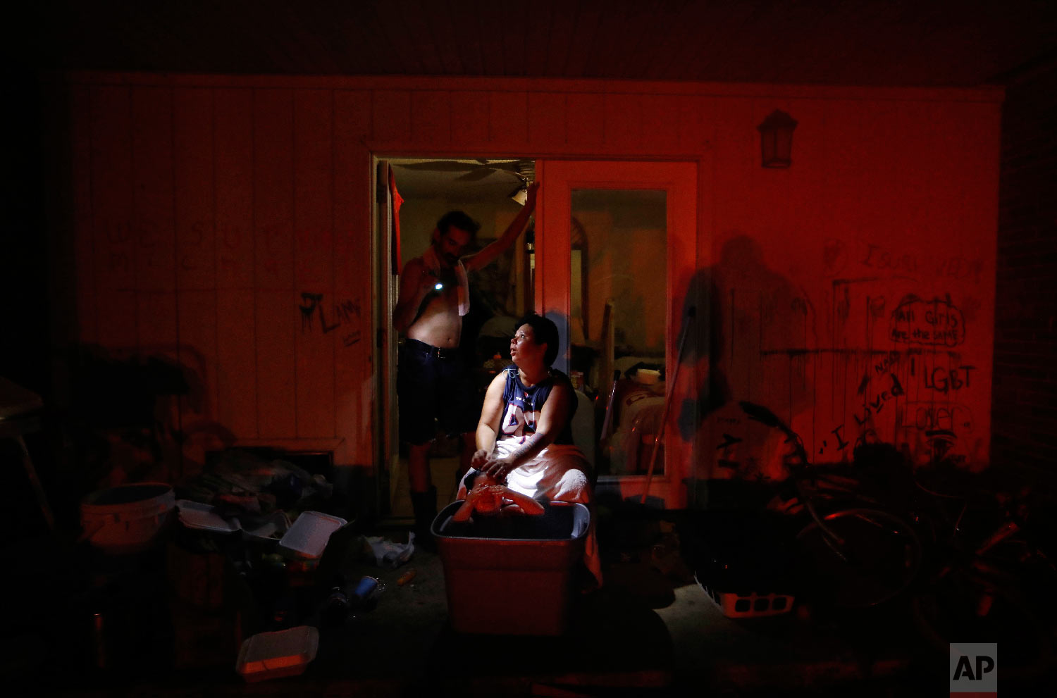 Tasha Hughes, bathes her daughter, Madison, 4, as Jeffrey Dumich holds a flashlight outside their room at the damaged American Quality Lodge where they continue to live without power in the aftermath of Hurricane Michael, in Panama City, Fla., Oct. 16, 2018. (AP Photo/David Goldman)