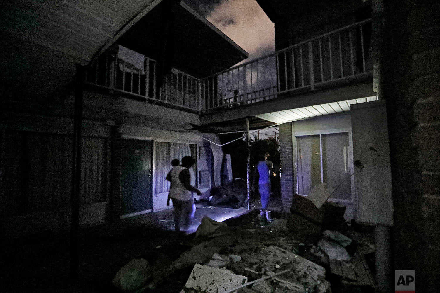 Residents walk past roofing debris at the damaged American Quality Lodge where they continue to live in the aftermath of Hurricane Michael in Panama City, Fla., Oct. 16, 2018. (AP Photo/David Goldman)