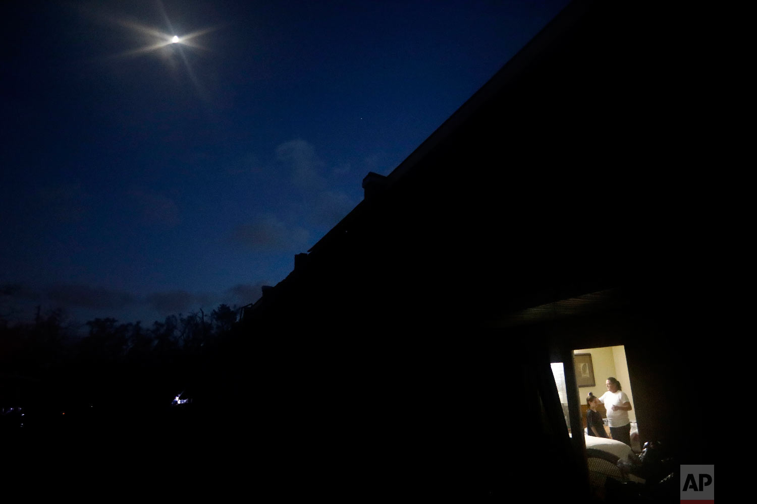 The moon shines above as Nola Davis, right, brushes the hair of granddaughter, Jayden Billingly, 10, before going to bed in their room at the damaged American Quality Lodge where they continue to live in the aftermath of Hurricane Michael, in Panama City, Fla., Oct. 16, 2018. (AP Photo/David Goldman)