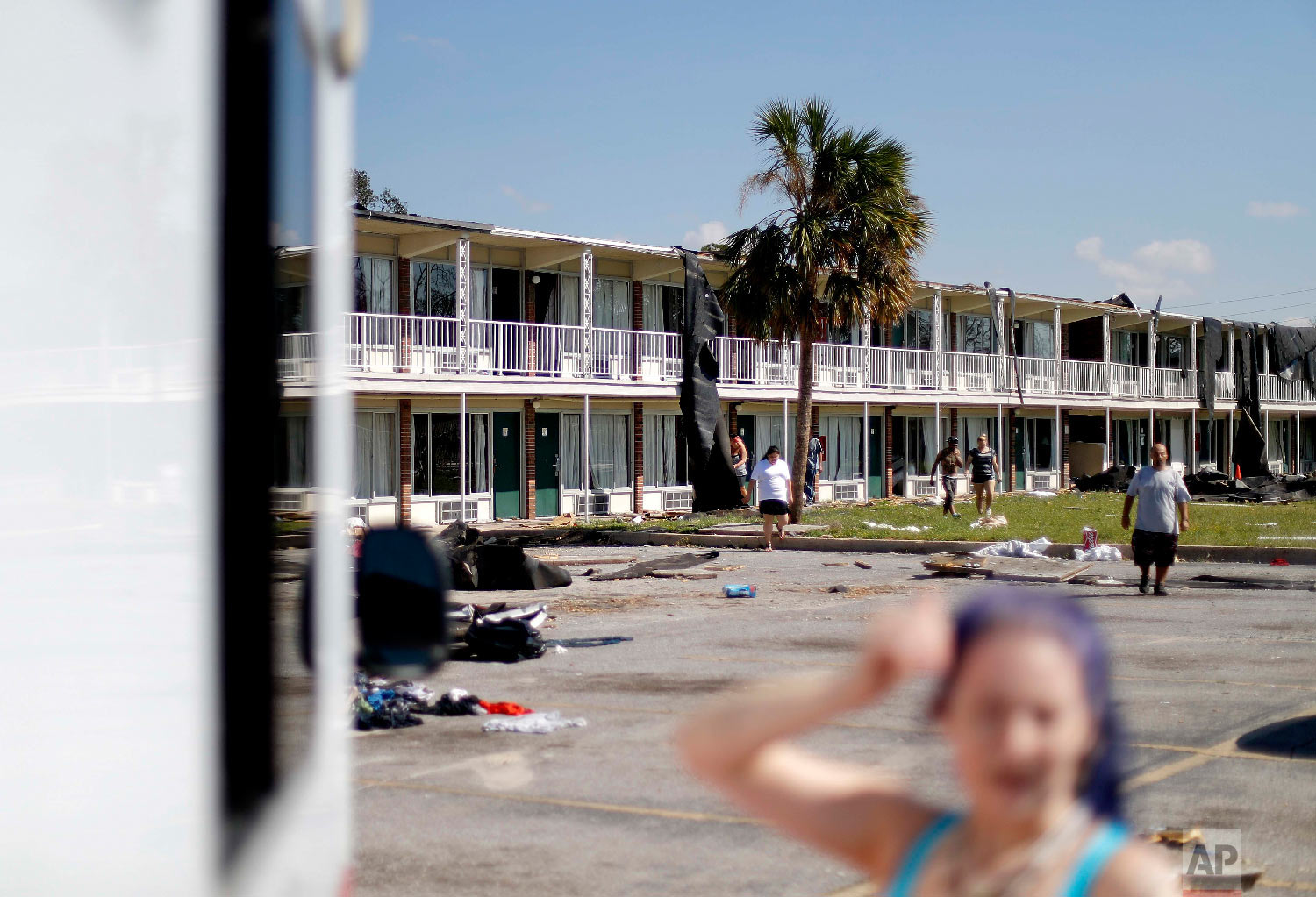 Residents walk in front of a damaged motel in Panama City on Oct. 16, 2018. (AP Photo/David Goldman)