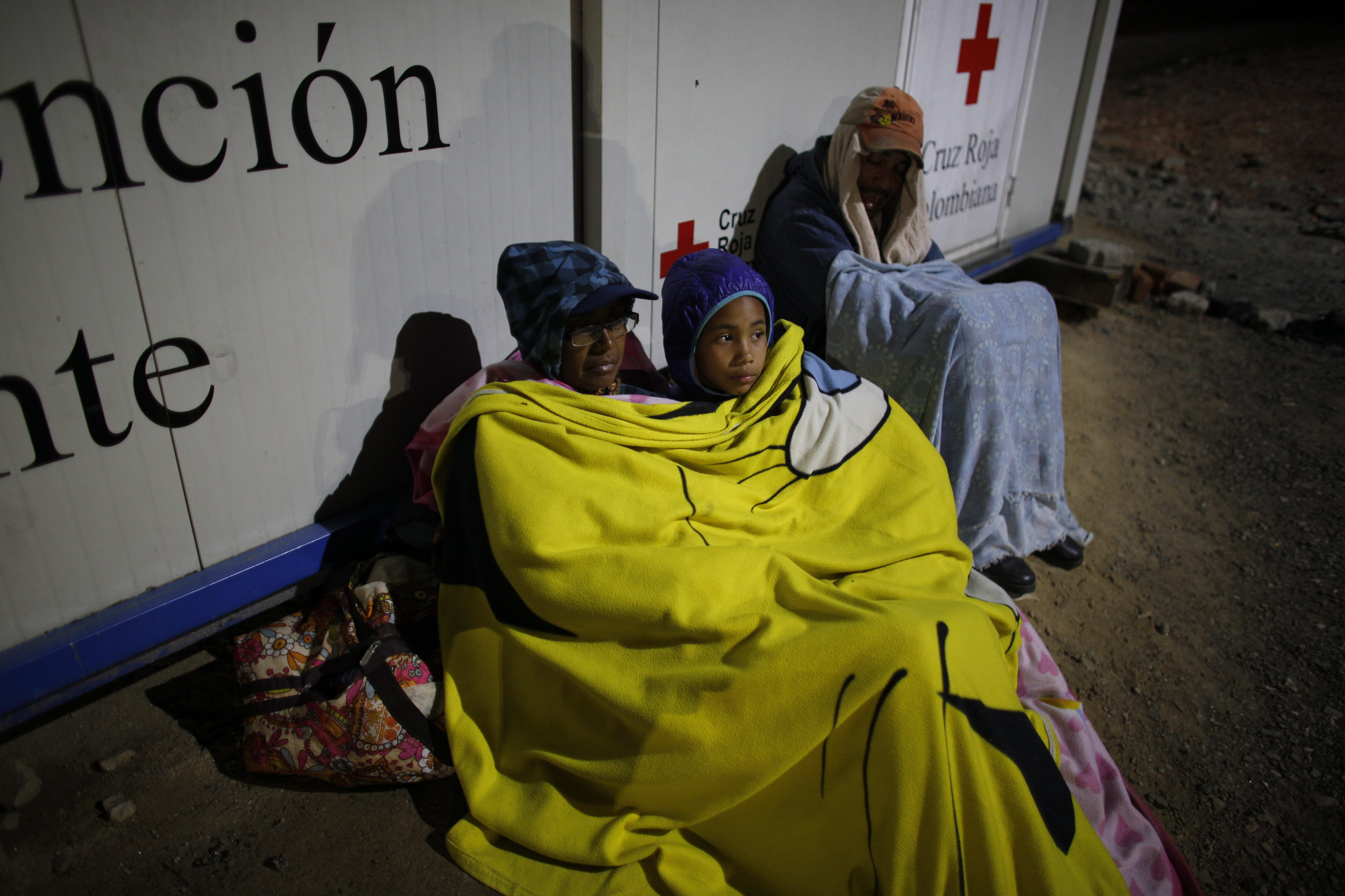 Sandra Cadiz rests with her daughter Angelis on a dirt floor near a gas station in Pamplona, Colombia, on their journey to Peru on Aug. 31, 2018. (AP Photo/Ariana Cubillos)