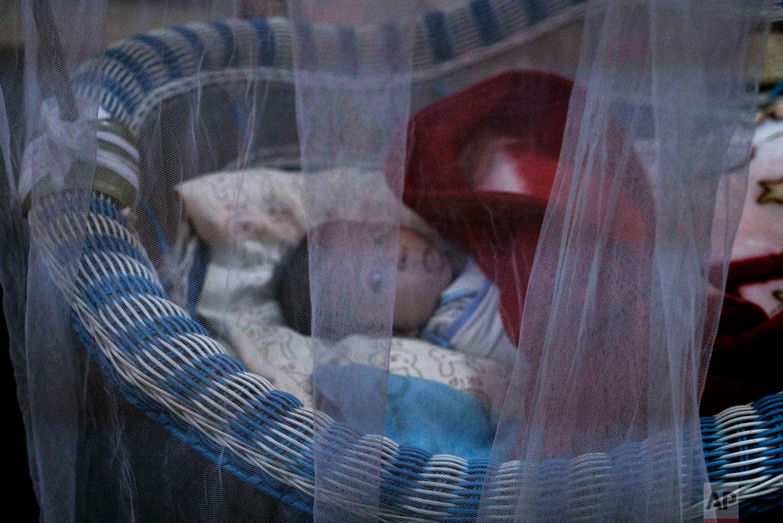 A newborn lies in her crib at the state-run al-Zuhour orphanage, in Mosul, Iraq. (AP Photo/Maya Alleruzzo)