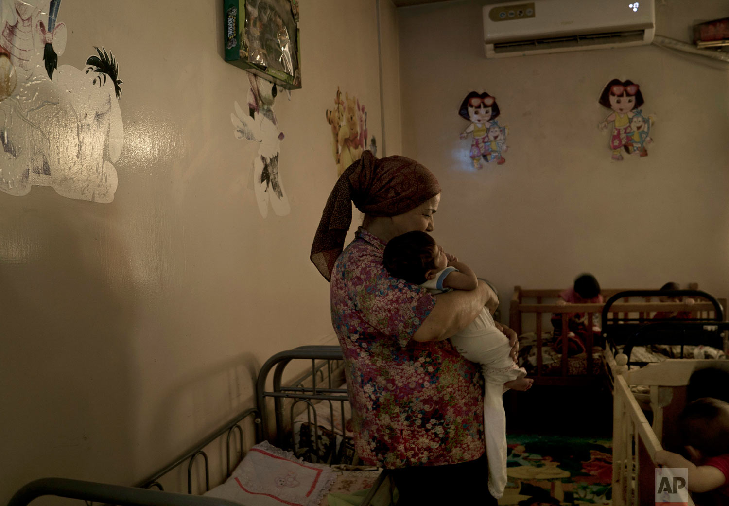 A caregiver soothes a newborn baby girl named Helen at the state-run Salhiya Orphanage in Baghdad, Iraq. (AP Photo/Maya Alleruzzo)