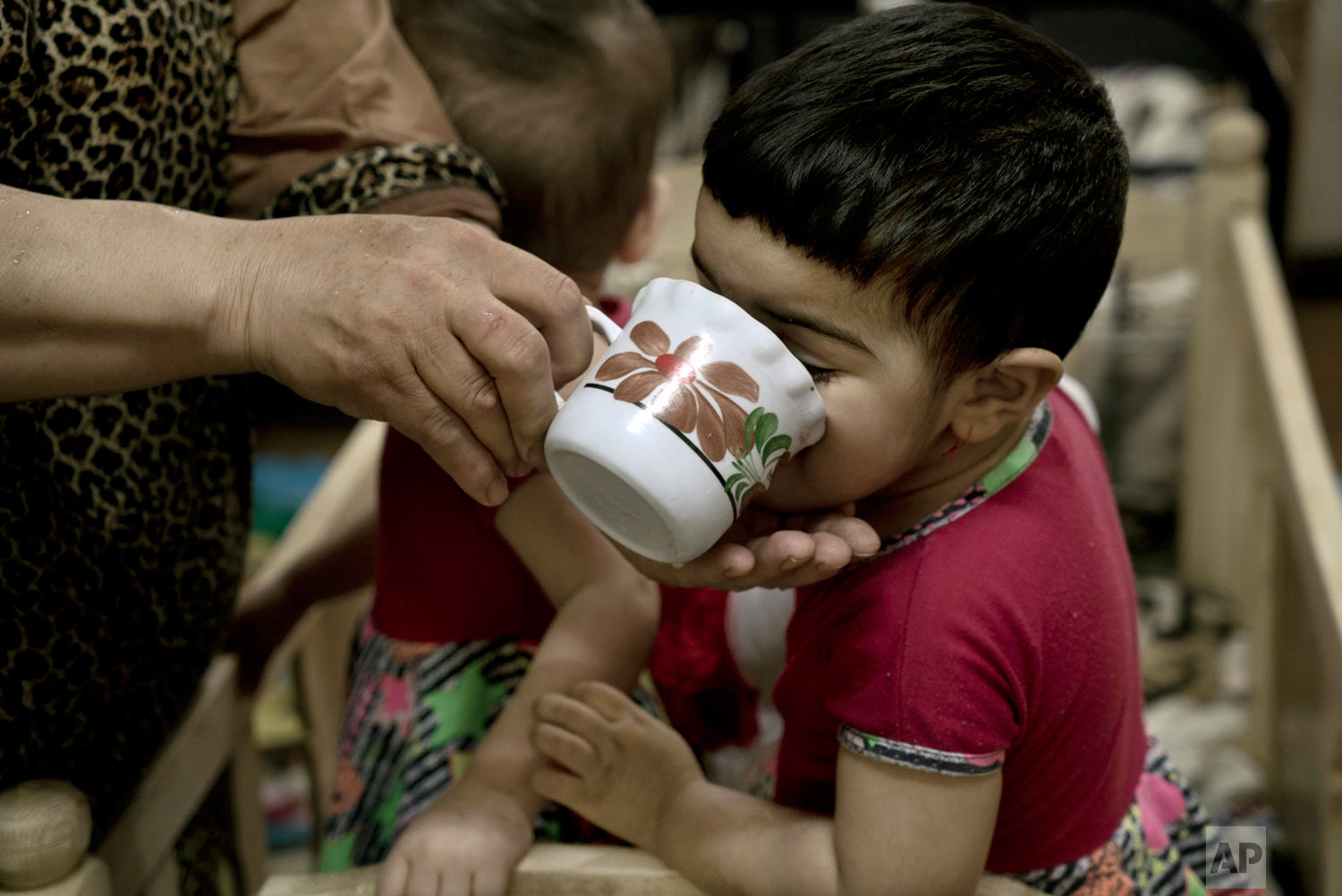 A toddler drinks from a cup at the state-run Salhiya Orphanage, which now hosts foreign and Iraqi children orphaned by Islamic State militants and the battle to oust them, in Baghdad, Iraq. (AP Photo/Maya Alleruzzo)