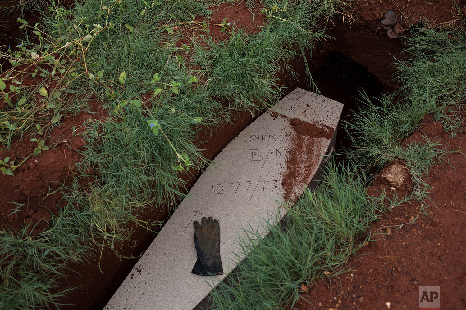 In this Thursday, April 12, 2018 photo, a glove sits on top of the coffin of an unidentified male at the Olifantsvlei cemetery outside Johannesburg. (AP Photo/Bram Janssen)