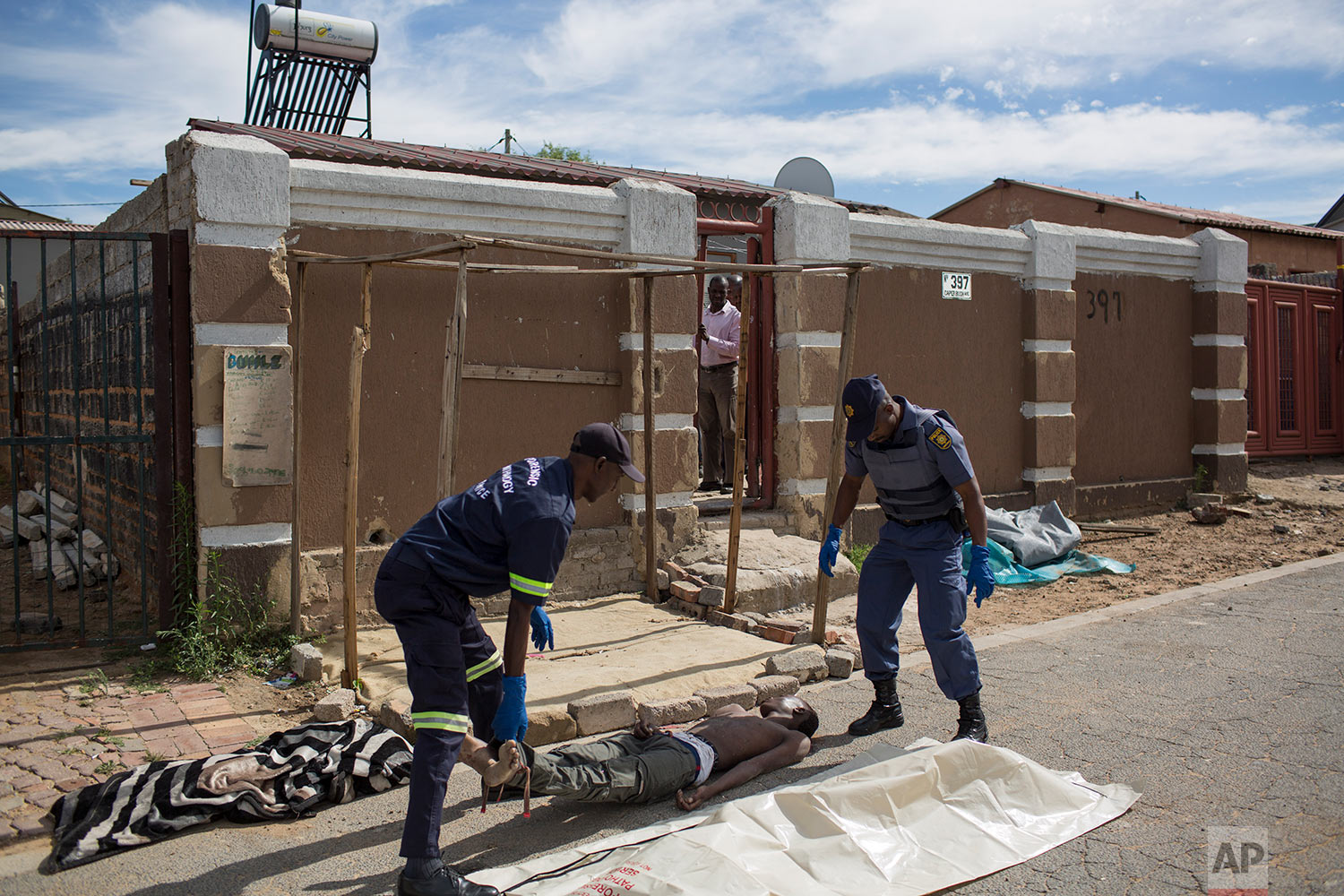 In this Sunday, Jan. 28, 2018 photo, a man killed in mob justice in Johannesburg is carried away to be transported to a mortuary. (AP Photo/Bram Janssen)