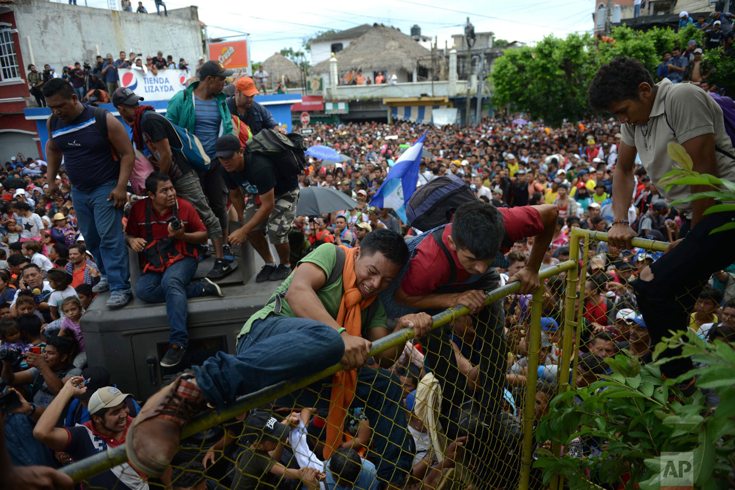 Thousands of Honduran migrants gather at a fence as some climb towards Mexico in Tecun Uman, Guatemala, Friday, Oct. 19, 2018. Migrants broke down the gates at the border crossing and began streaming toward a bridge into Mexico. After arriving at the tall, yellow metal fence some clambered atop it and on U.S.-donated military jeeps. Young men began violently tugging on the barrier and succeeded in tearing it down. (AP Photo/Oliver de Ros)