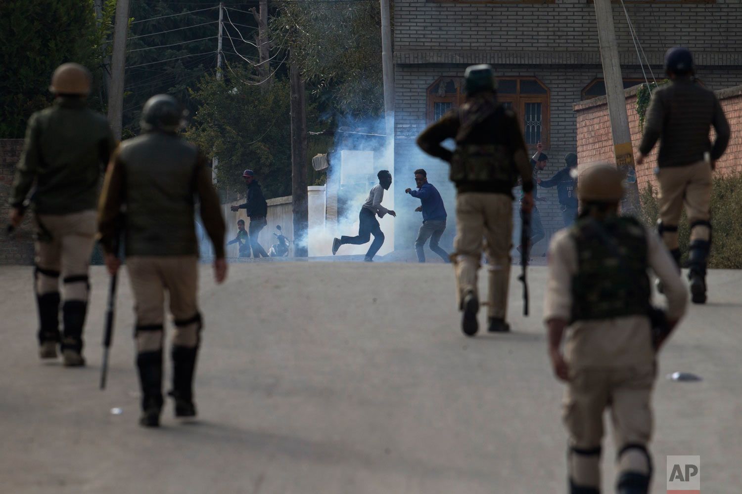 Kashmiri protesters run for cover from a tear gas shell fired at them by Indian security forces in Srinagar, India, Friday, Oct. 19, 2018. Government forces fired tear gas and pellets on Kashmiris who gathered after Friday afternoon prayers on a protest call given by separatists against the killing two rebels and a civilian during a gun battle in Srinagar on Wednesday. (AP Photo/Dar Yasin)