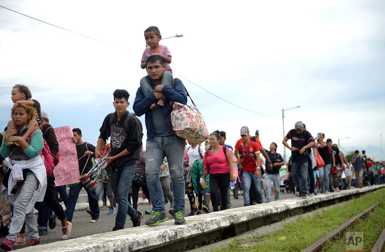 Thousands of Honduran migrants rush across the border towards Mexico, in Tecun Uman, Guatemala, Friday, Oct. 19, 2018. (AP Photo/Oliver de Ros)