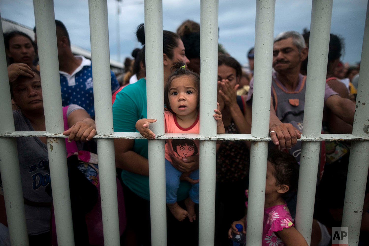 Migrants bound for the U.S.-Mexico border wait on a bridge that stretches over the Suchiate River, connecting Guatemala and Mexico, in Tecun Uman, Guatemala, Friday, Oct. 19, 2018. (AP Photo/Oliver de Ros)
