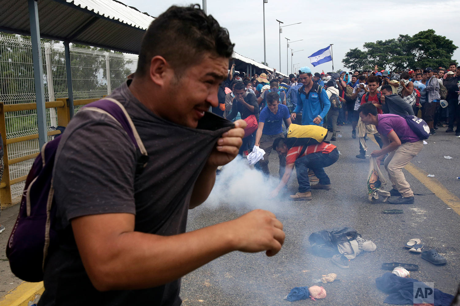 Men attempt to grab a tear gas canister thrown by the Mexican Federal Police, after Central American migrants rushed the gate at the border crossing in Ciudad Hidalgo, Mexico, Friday, Oct. 19, 2018. (AP Photo/Moises Castillo)