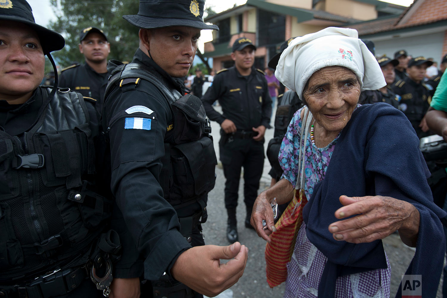 An elderly Honduran migrant woman talks with Guatemalan police who temporarily block the road to keep her and her caravan from advancing, in Esquipulas, Guatemala, Monday, Oct. 15, 2018. (AP Photo/Moises Castillo)