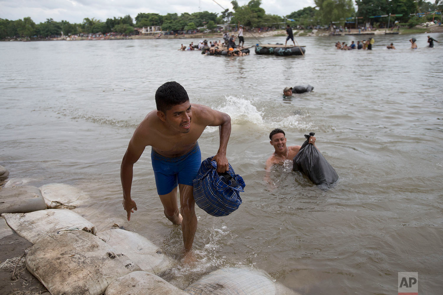 Central American migrants reach the shore on the Mexican side of the Suchiate River after wading across, on the the border between Guatemala and Mexico, in Ciudad Hidalgo, Mexico, Saturday, Oct. 20, 2018. (AP Photo/Moises Castillo)