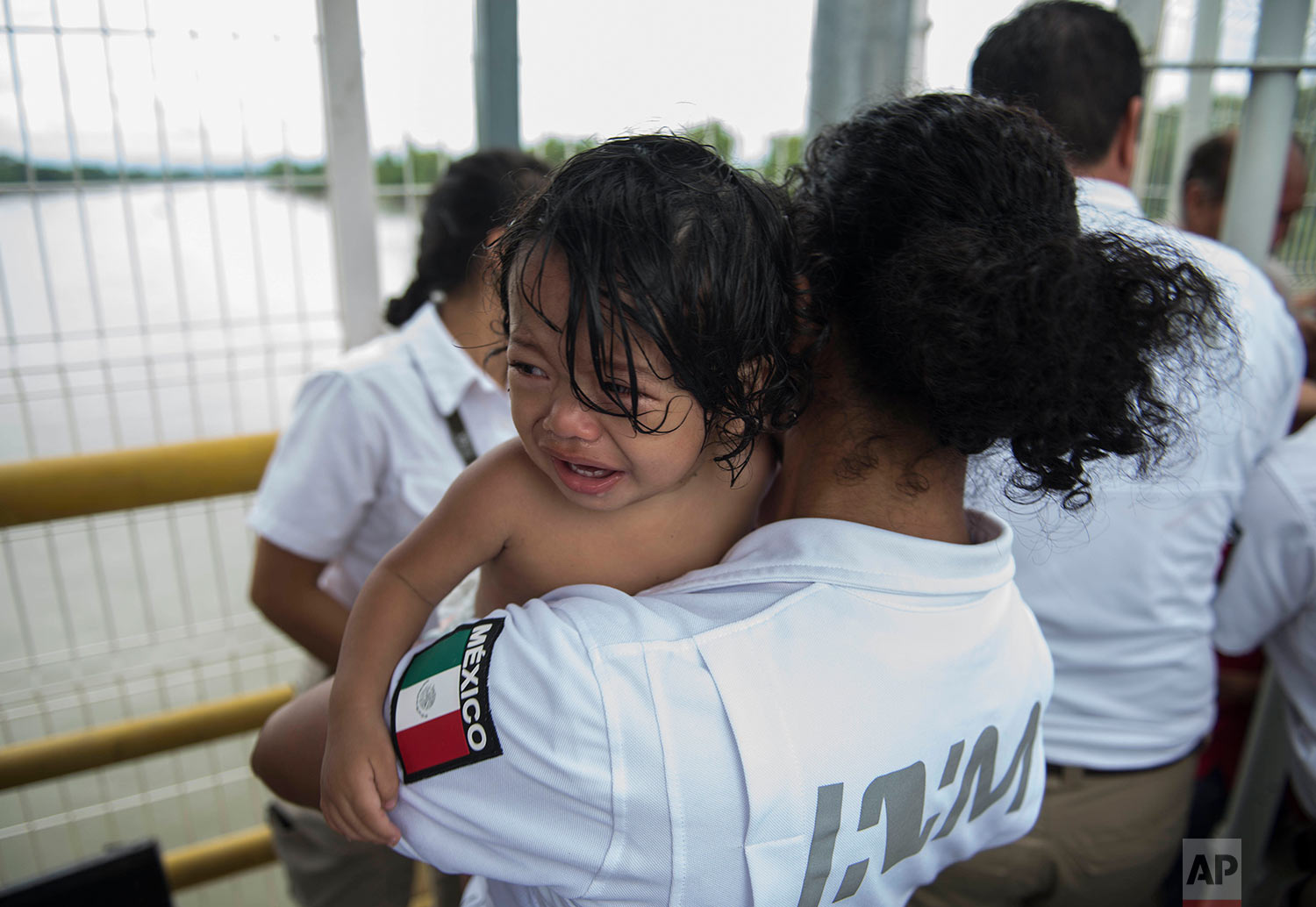 A Honduran migrant child held by a Mexican immigration worker, cries after crossing the border between Guatemala and Honduras with his family, in Ciudad Hidalgo, Mexico, Saturday, Oct. 20, 2018. (AP Photo/Oliver de Ros)