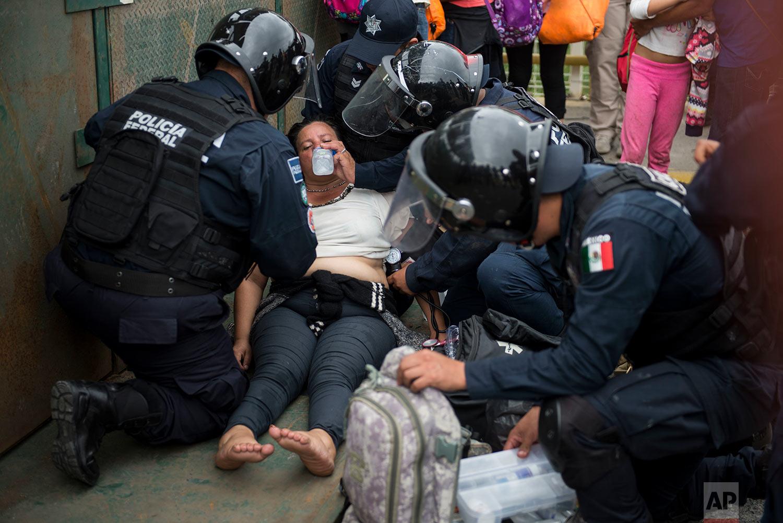 Mexican paramedics help a Honduras migrant woman who fainted after crossing the border between Guatemala and Mexico, in Ciudad Hidalgo, Mexico, Saturday, Oct. 20, 2018.  (AP Photo/Oliver de Ros)