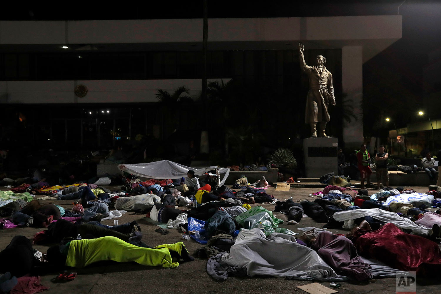 Honduran migrants hoping to reach the U.S. sleep in the southern Mexico city of Tapachula, Monday, Oct. 22, 2018, in a public plaza featuring a statue of Mexican national hero Miguel Hidalgo, a priest who launched Mexico's War of Independence in 1810. (AP Photo/Moises Castillo)