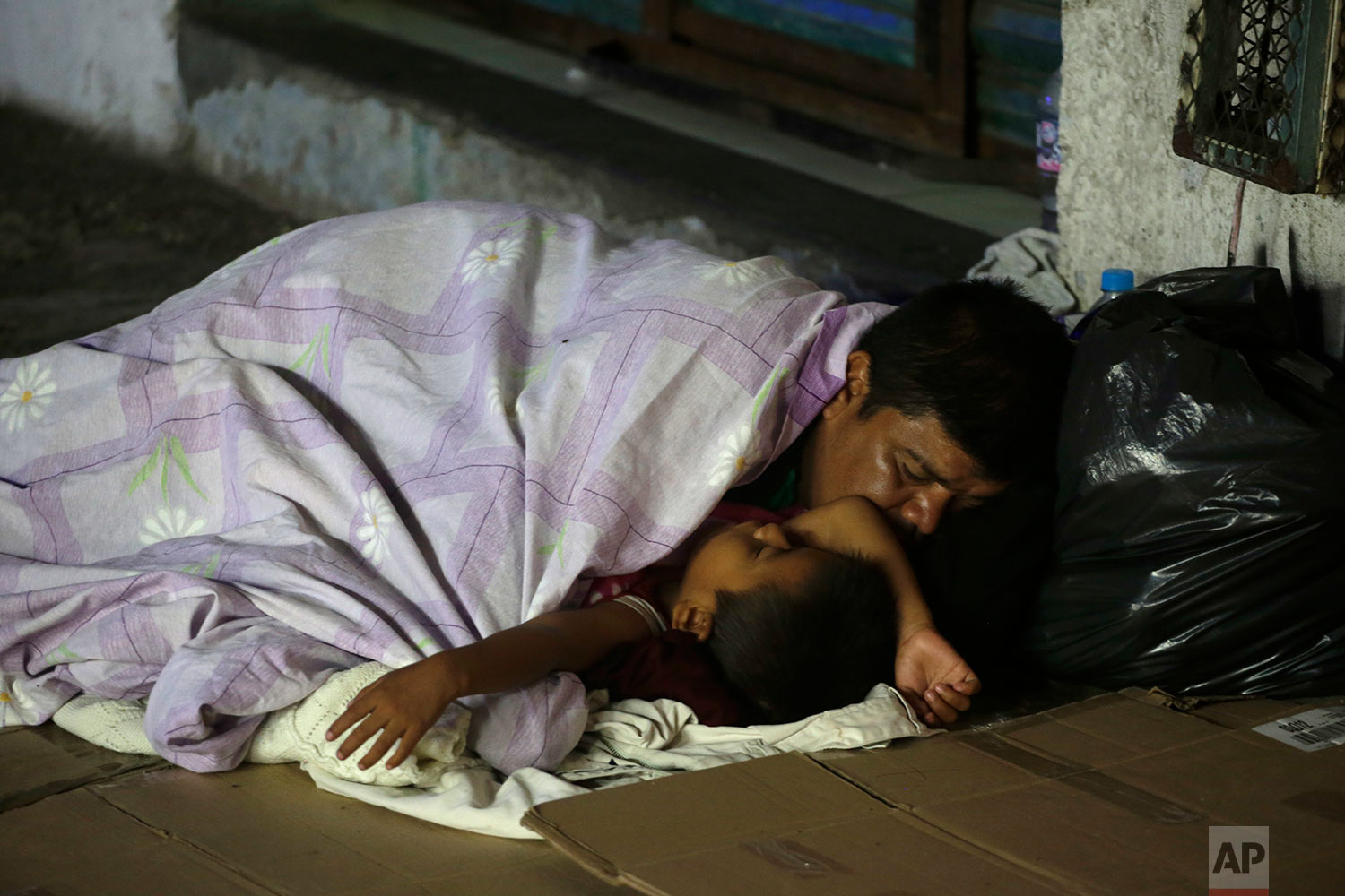 Honduran migrants hoping to reach the U.S. sleep on a sidewalk in the southern Mexico city of Tapachula, Monday, Oct. 22, 2018. (AP Photo/Moises Castillo)