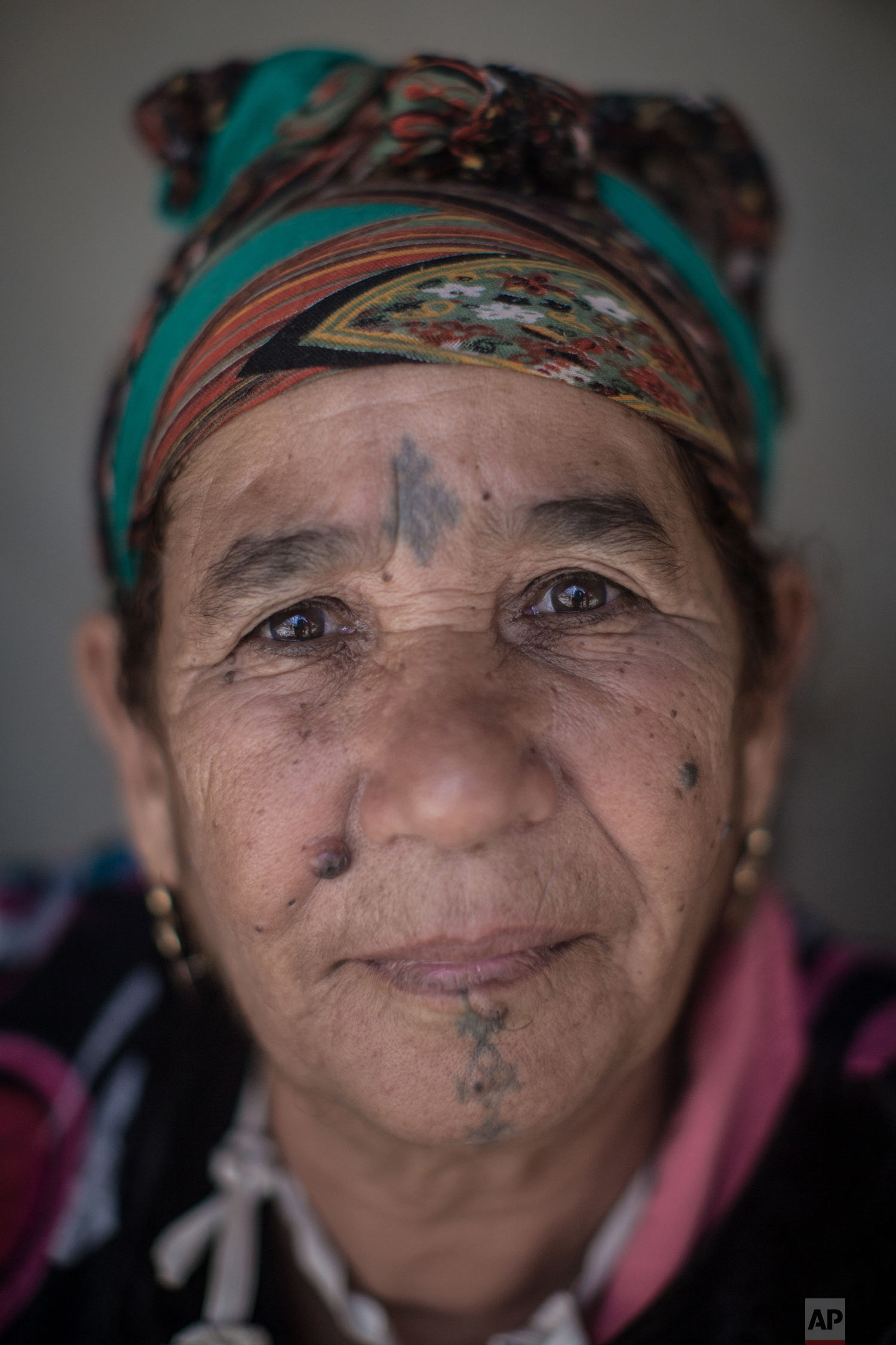 In this Saturday, Oct. 13, 2018 photo, Fatima Hadeoui, 63, poses for a portrait displaying her face tattoo, in the Middle Atlas town of Anergui, near Azilal, central Morocco. (AP Photo/Mosa'ab Elshamy)