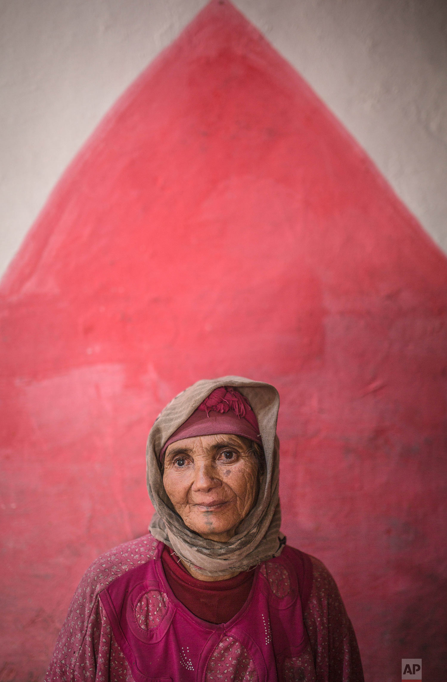 In this Saturday, Oct. 13, 2018 photo, Etto Elchafai, 63, poses for a portrait displaying her face tattoo, in the town of Tinguerf, near Azilal, central Morocco. (AP Photo/Mosa'ab Elshamy)