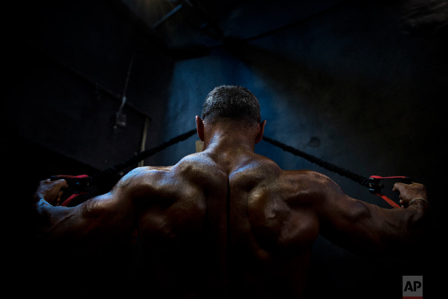 A contestant exercises backstage during the National Amateur Body Builders' Association competition in Tel Aviv, Israel on Oct. 18, 2018. (AP Photo/Oded Balilty)