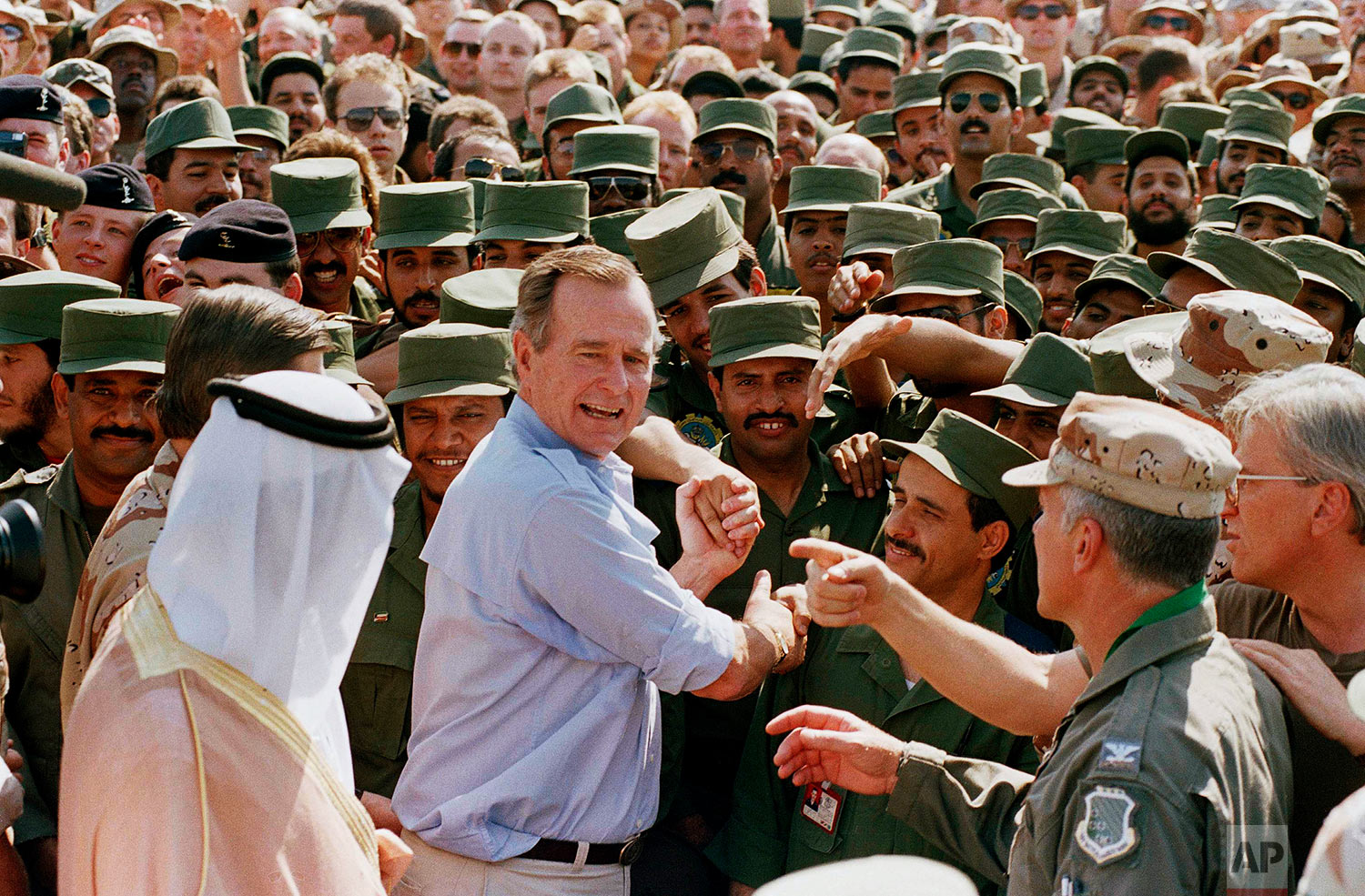 President George Bush is greeted by Saudi troops and others as he arrives in Dhahran, Saudi Arabia, for a Thanksgiving visit, Nov. 22, 1990. (AP Photo/J. Scott Applewhite)