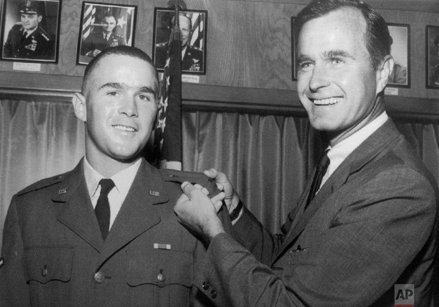 In this 1968 photo provided by the Texas National Guard, George H.W. Bush, right, is about to pin a lieutenant bar on his son, George W. Bush, after the younger Bush was made an officer in the Texas Air National Guard in Ellington Field, Texas. (Texas National Guard via AP)