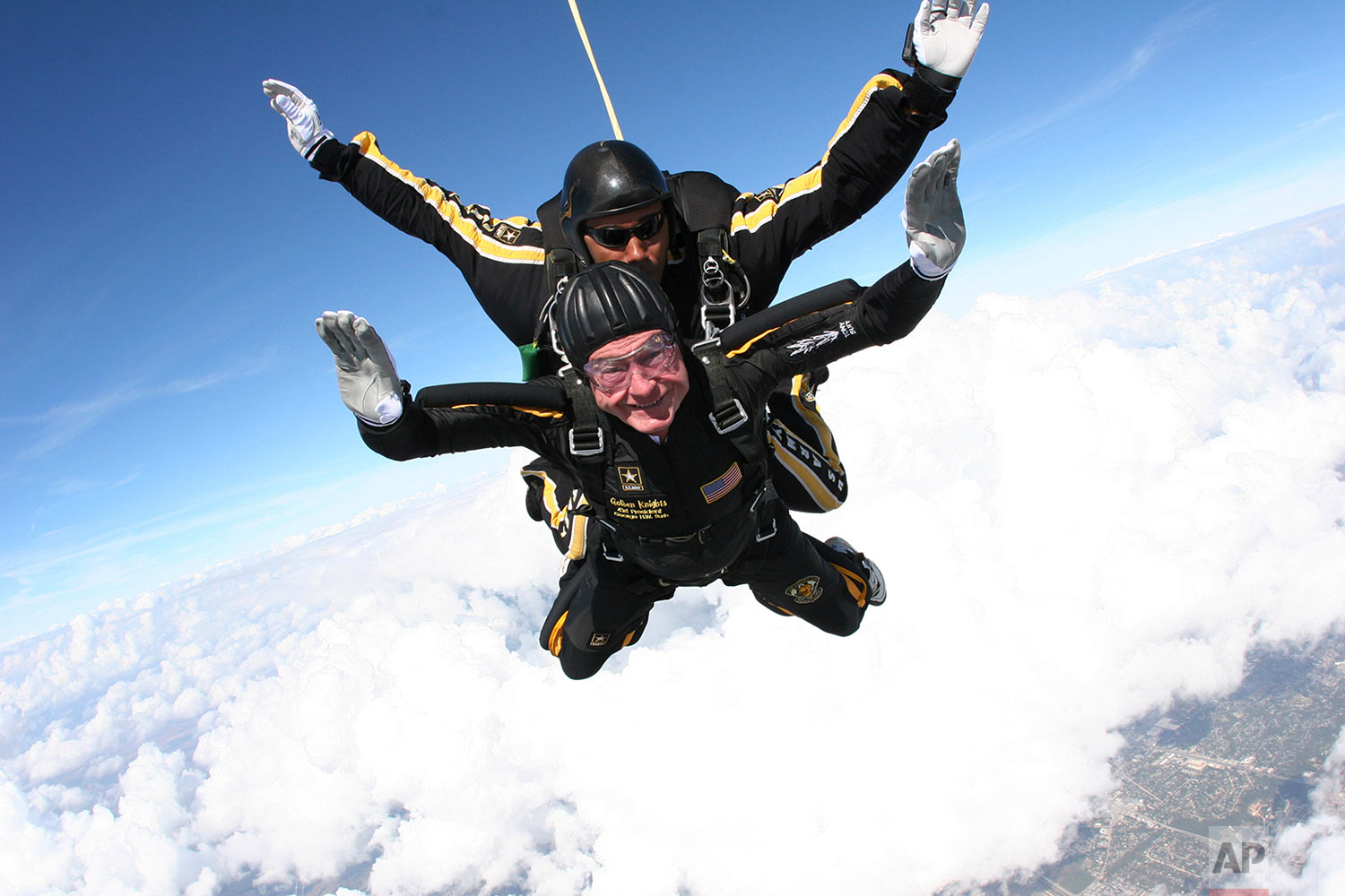 In this provided by the U.S. Army Golden Knights, former President George H.W. Bush free falls with Golden Knights parachute team member Sgt. 1st Class Mike Elliott, as he makes a dramatic entrance to his presidential museum on Nov. 10, 2007, during a rededication ceremony in College Station, Texas. (Sgt. 1st Class Kevin McDaniel/U.S. Army via AP)