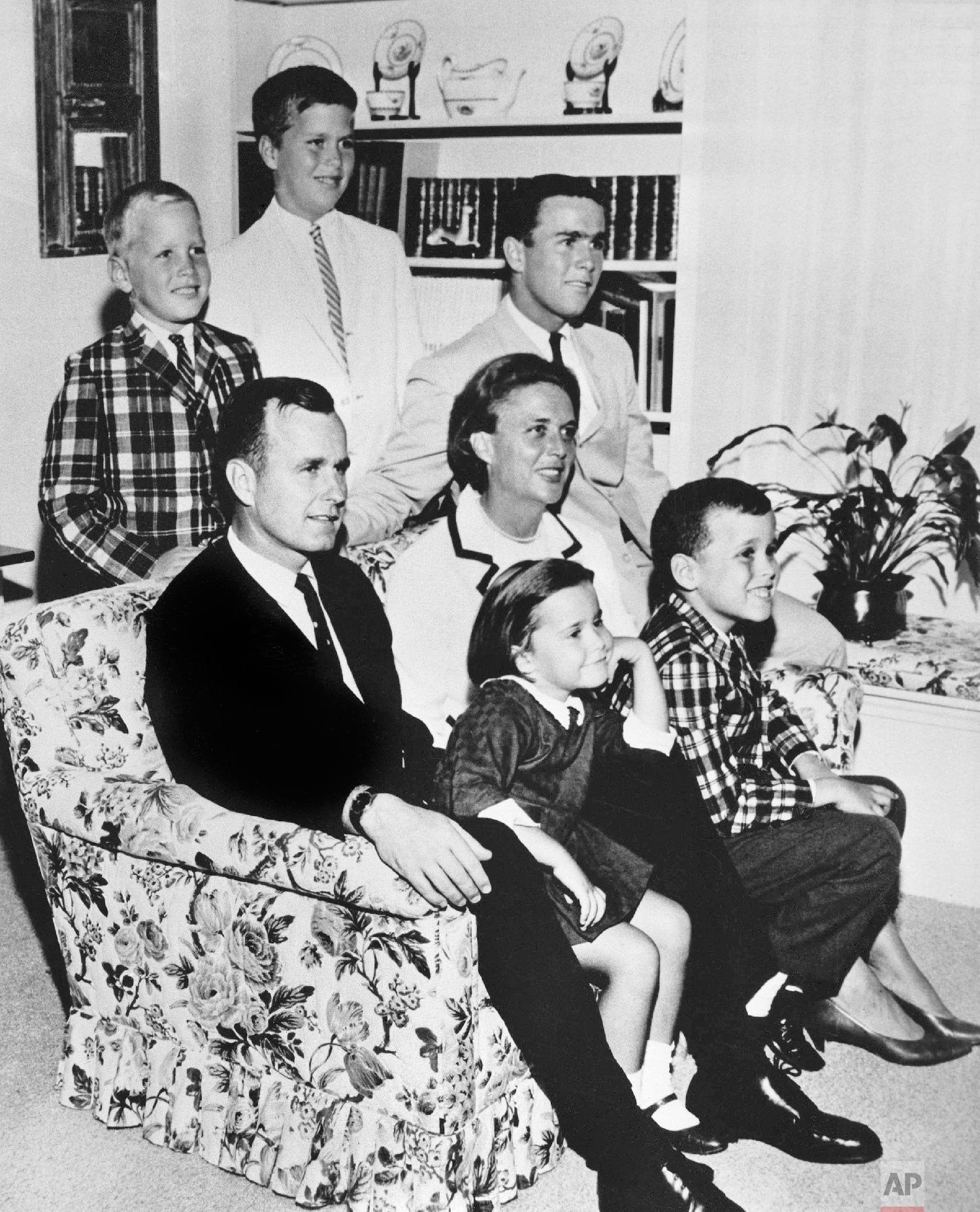 George H.W. Bush sits on a couch with his wife Barbara and their children in 1964. George W. Bush sits at right behind his mother. Behind the couch are Neil and Jeb Bush. Sitting with parents are Dorothy and Marvin Bush. (AP Photo)
