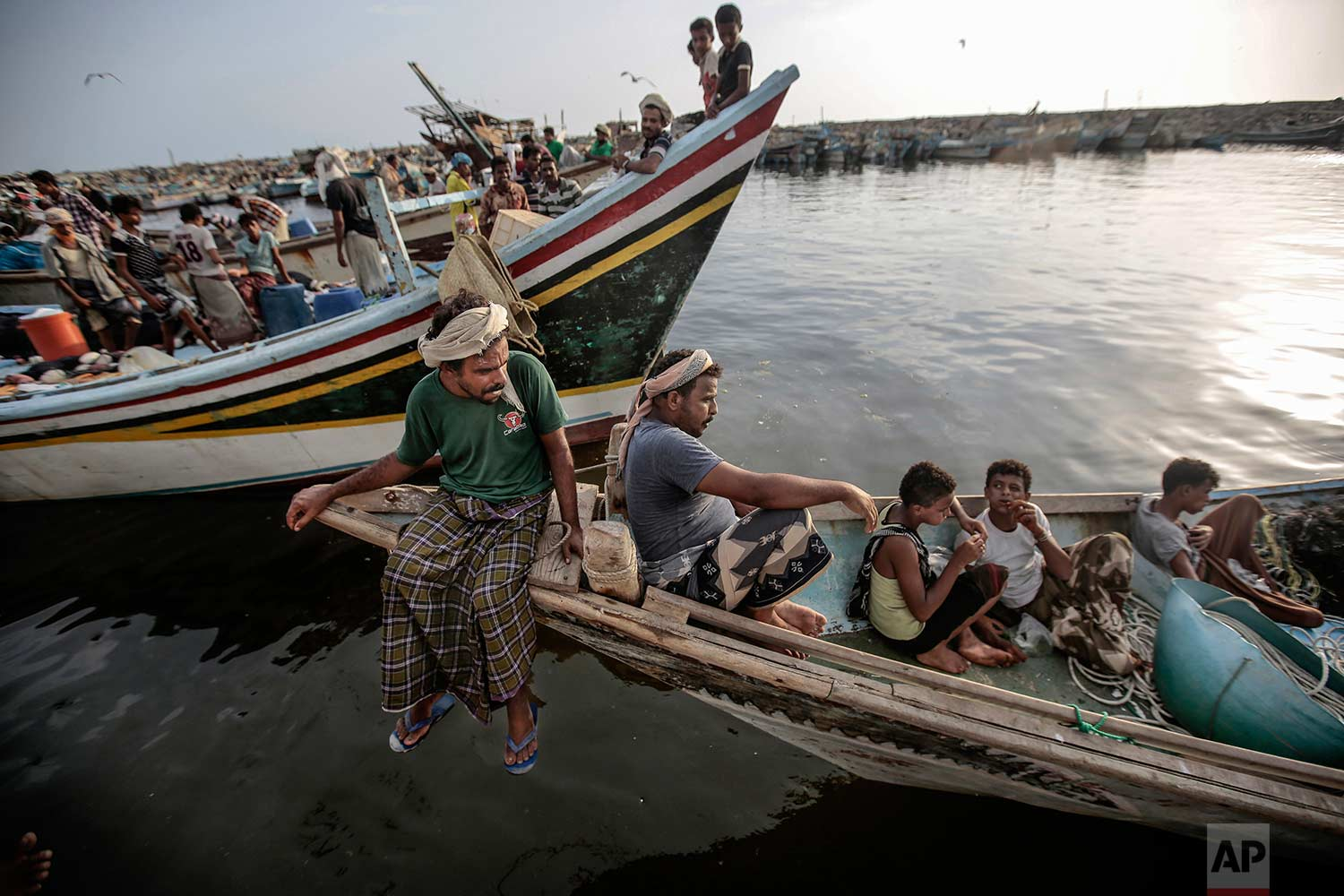 In this Sept. 29, 2018, photo, fishermen rest on their boats before working at the main fishing port, in Hodeida, Yemen. (AP Photo/Hani Mohammed)