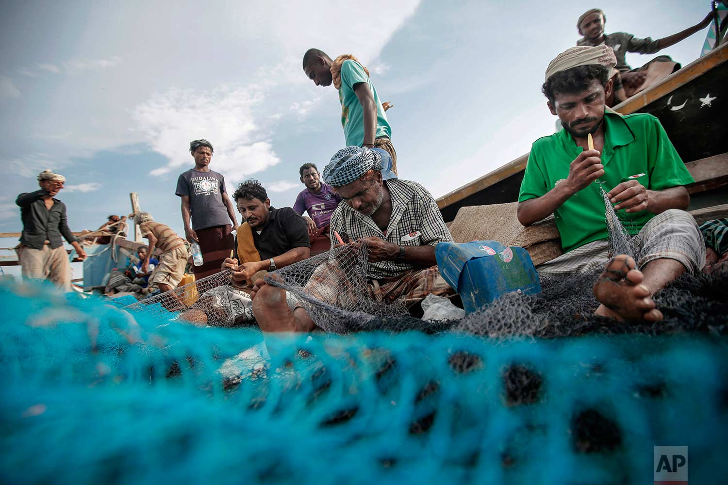 In this Sept. 29, 2018, photo, fishermen work on their nets before a fishing trip at the main fishing port, in Hodeida, Yemen. (AP Photo/Hani Mohammed)