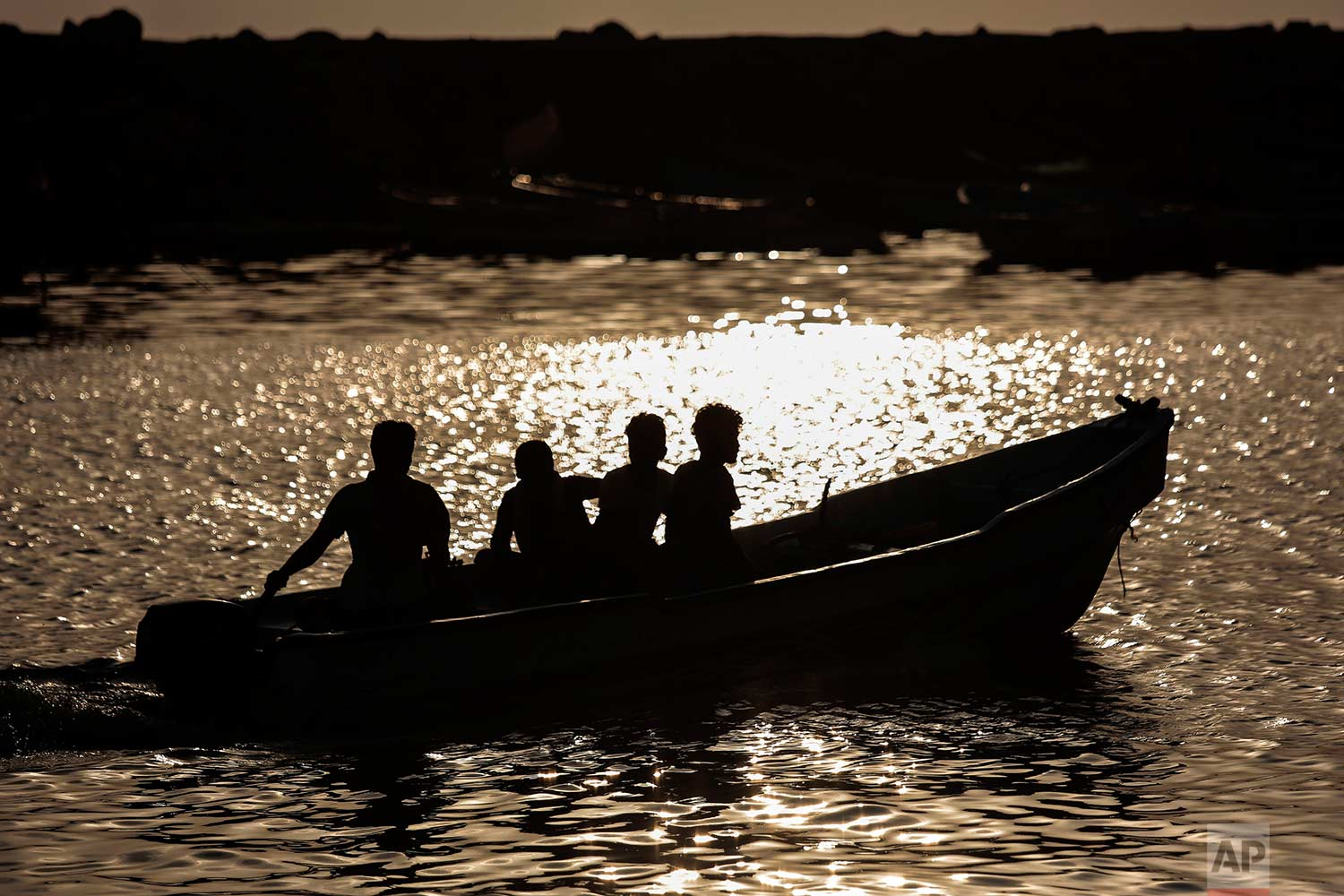 In this Sept. 29, 2018, photo, fishermen head out to sea for a fishing trip as the sun sets near the fishing port, in Hodeida, Yemen. (AP Photo/Hani Mohammed)