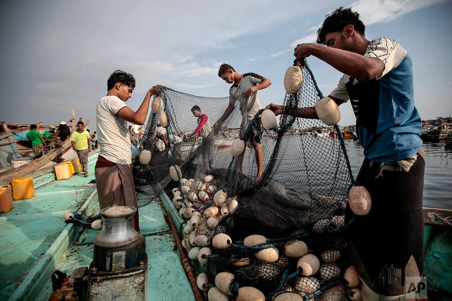 In this Sept. 29, 2018 photo, Yemeni fishermen load their nets on to a boat before a fishing trip at the main fishing port, in Hodeida, Yemen. (AP Photo/Hani Mohammed)