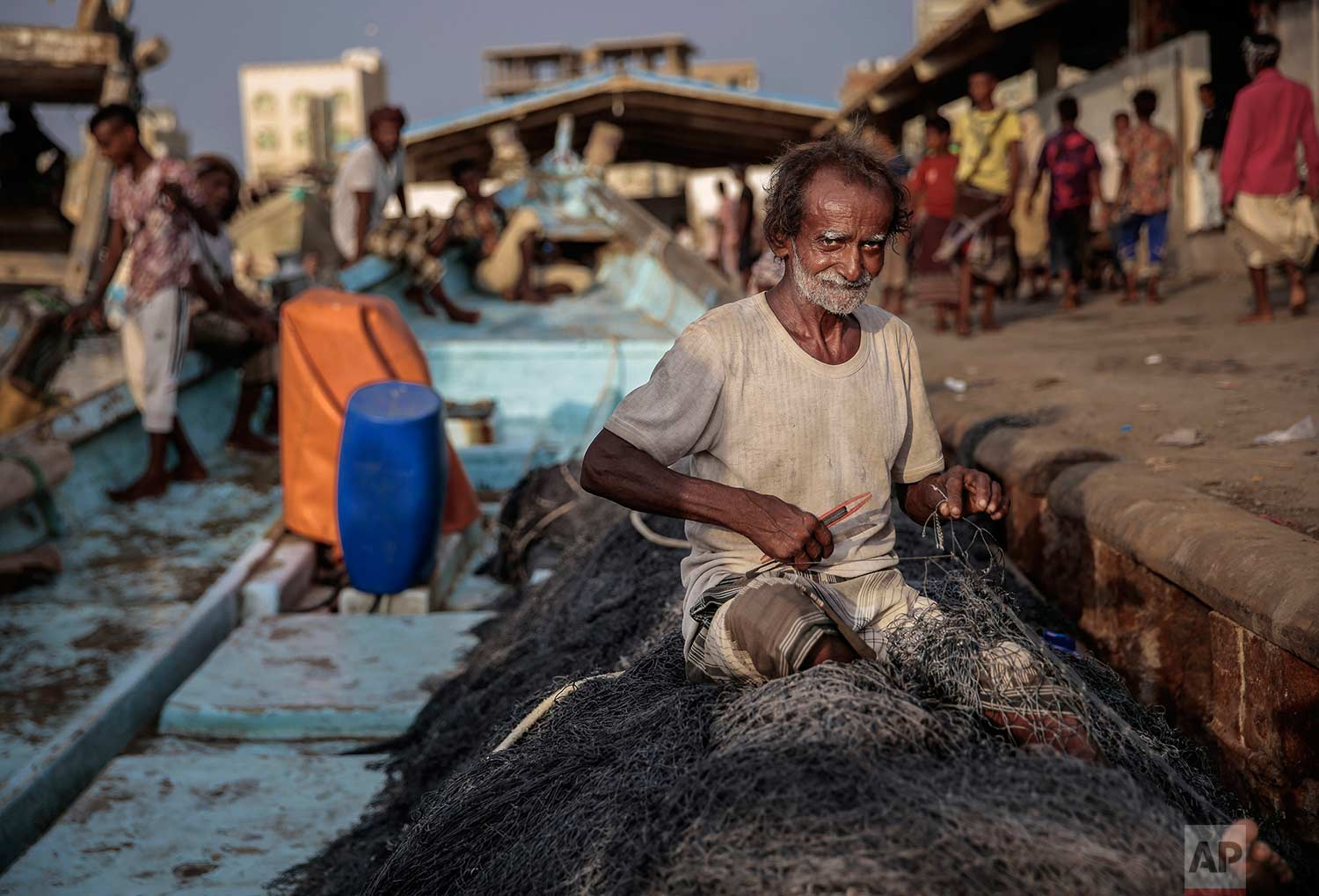 In this Sept. 29, 2018, photo, 71-year-old Yemeni fisherman Ammar Ahmed prepares his nets before a fishing trip at the main fishing port, in Hodeida, Yemen. (AP Photo/Hani Mohammed)