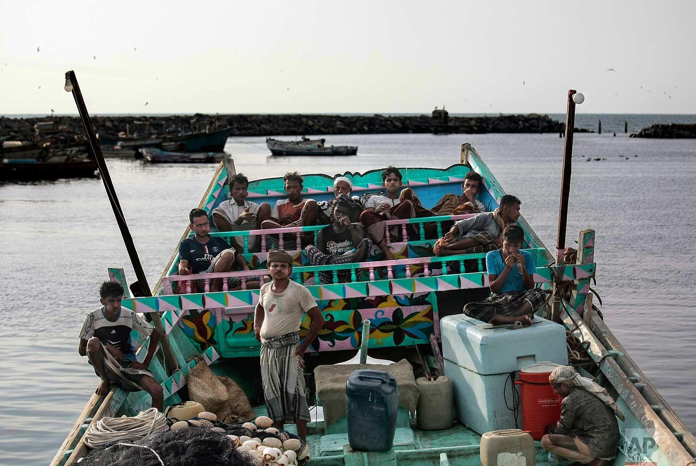 In this Sept. 29, 2018, photo, fishermen take a break and chew Qat, an amphetamine-like stimulant, on a boat at the main fishing port, in Hodeida, Yemen. (AP Photo/Hani Mohammed)